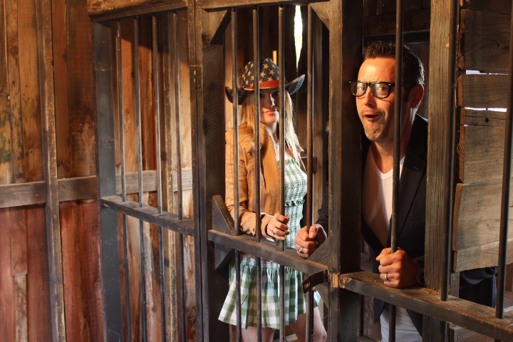 Couple posing in jail cell during a corporate event at Enchanted Springs Ranch
